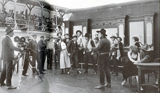 "Paying customers in the bleachers watch the filming of ""Love's Lariat"" ('16 Bluebird) starring Harry Carey Sr., seen in the center holding a gun on a badman while protecting Olive Fuller Golden, better known as Carey's wife. Film was made at Universal's California studio."