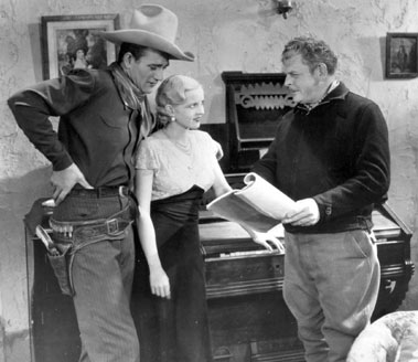 "Director Robert North Bradbury goes over a plot point in the script of ""Texas Terror"" ('35 Lone Star) with John Wayne and Lucile Browne."