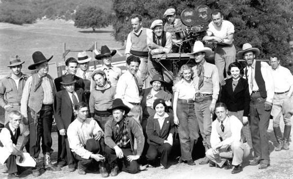 "Cast and crew of ""Sundown Trail"" ('34 Imperial). Star Wally Wales has his arm around leading lady Fay McKenzie. Director Bob Tansey is the tall man in the white shirt in the middle. His brother, actor James Sheridan (aka Sherry) Tansey stands on the far right next to the lady in the black jacket. Others unknown. (Thanx to Jerry Whittington.)"