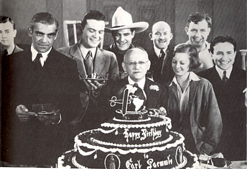 Celebrating Universal honcho Carl Laemmle's 67th birthday in January 1934 are (l-r) James Scott, Boris Karloff, Hugh Enfield, Ken Maynard, Laemmle, Vince Barnett, Margaret Sullivan, Andy Devine and Carl Laemmle Jr.