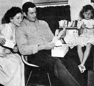 Clint Walker and his wife at the time, Verna Lucille, and daughter Valerie Jean, glance through fan mail in 1958.