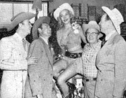 "Eddie Dean, Tex Williams, Nudie and Rex Allen look up to the charms of starlet Kathy Marlowe (""The Big Trees"", ""Bounty Hunter"", ""Sudden Danger"", ""Burns and Allen Show"", ""Five Bold Women""). Circa 1959."
