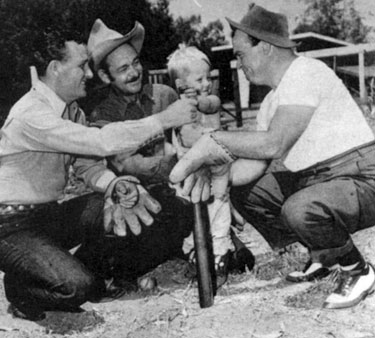 "When he's not making westerns for Monogram, Jimmy Wakely relaxes with friends and his son Johnny playing sandlot baseball or fishing. In this photo Jimmy, screen heavy Ted French, Jimmy's 3 year old son Johnny and sidekick Dub ""Cannonball"" Taylor get ready for a game."