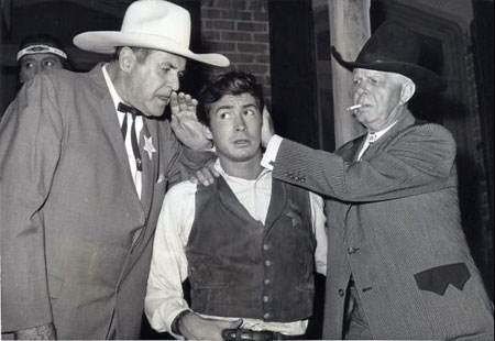 "Ken Maynard offers words of wisdom to Tony Perkins who was set to star in ""Tin Star"" ('57 Paramount). Those wisdom words won't be going out the other ear, Hoot Gibson is seeing to that. The two western greats, along with other former movie cowboys, attended a barbecue hoedown at Paramount hosted by Perkins to promote ""Tin Star"" which co-starred Henry Fonda. (Thanx to Jerry Whittington.)"