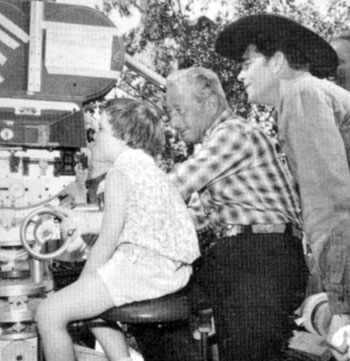 "Dale Robertson's daughter, Rochelle, gets a few camera pointers from a ""Tales of Wells Fargo"" cameraman and dad Dale. Taken in late 1959."