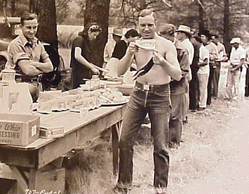 Gene savors a slice of watermelon while on location lunch break. Note Smiley Burnette further back in line. (Thanx to Jerry Whittington.)