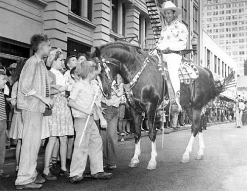 Gene and Champion greet children on the streets of Houston during the January 29, 1947, Houston Fat Stock Show Rodeo parade.