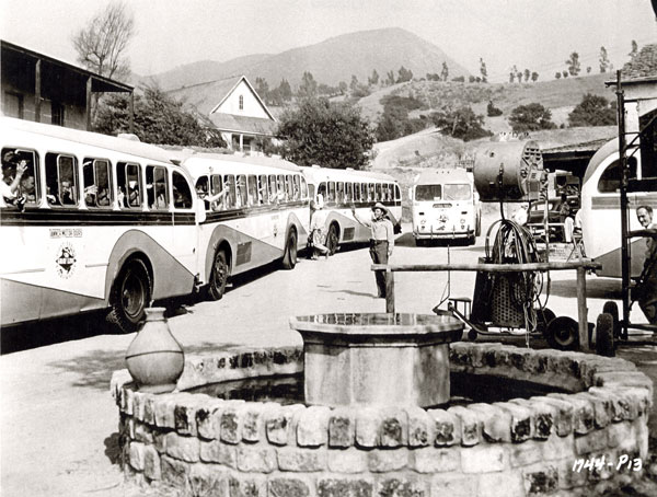 "While making ""Ride Clear of Diablo"" ('53), Audie Murphy greets busloads of tourists on the Universal backlot."