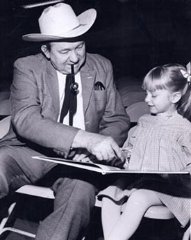 Tex Ritter helps young Heather Moore read her storybook backstage while waiting to go on for a show at the Denver Red Rocks Amphitheater.