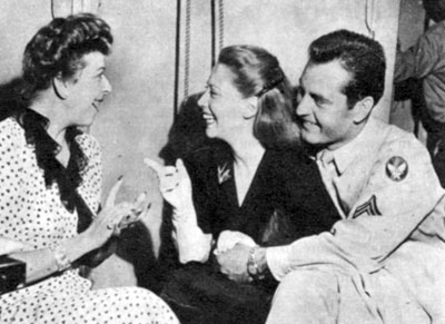 Army Air Corps Corporal George Montgomery listens while wife Dinah Shore talks with radio's Baby Snooks (Fannie Brice) in late 1944. George and Dinah were married from December 5, 1943 til May 9, 1963.