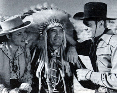 "Kay Aldridge, Chief Thunder Cloud and Allan Lane chat while making Republic's ""Daredevils of the West"" serial ('43)."