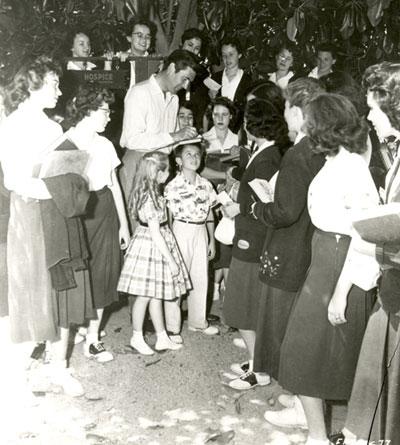 Fess Parker signs autographs for a group of female fans.