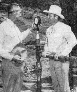 Gene Autry watches the gage on a Wichita Falls oil well with his co-owner S. D. Johnson of Wichita Falls. Circa late '40s.