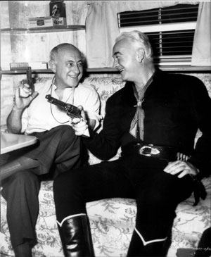 Director Cecil B. DeMille and Hopalong Cassidy compare six shooters. (Thanx to Bobby Copeland.)