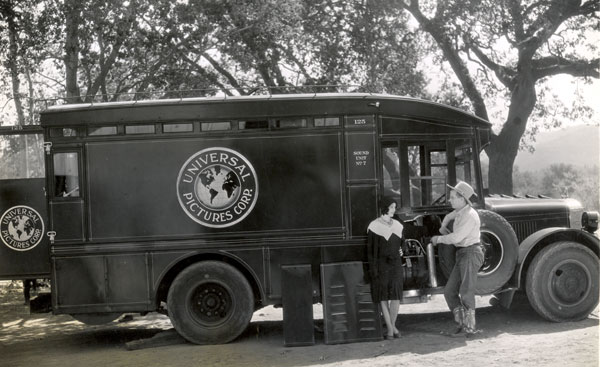 Hoot Gibson and his leading lady stand beside a Universal Sound truck in the early '30s.