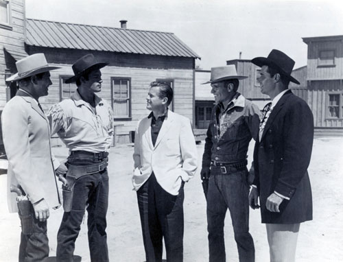 "On the Warner Bros. backlot producer Bill Orr (center) talks with Wayde (""Colt .45"") Preston, Clint (""Cheyenne"") Walker, Will (""Sugarfoot"") Hutchins and James (""Maverick"") Garner. (Thanx to Neil Summers.)"