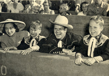 Rodeo fans all, lined up in front row seats...Dan Duryea with wife Helen and sons Peter (left) and Richard.