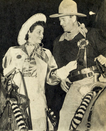 Rodeo Queen Jane Russell and Grand Marshal John Wayne compare their official badges as they wait for the Grand Entry Parade which they led.