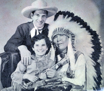 "Radio Red Ryder Reed Hadley smiles as his Little Beaver, Tommy Cook, is ""adopted"" by Chief Thunder Cloud circa 1942."