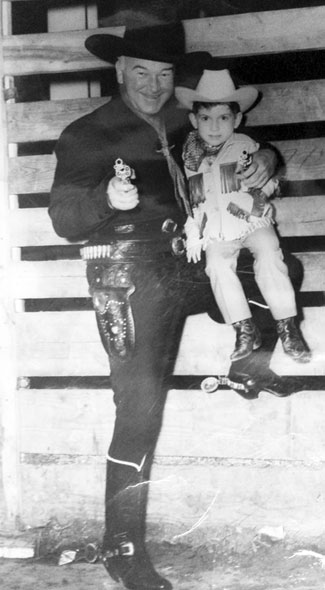 Hopalong Cassidy goes gunning with a young fan.