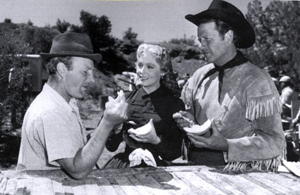 "Director Roy Rowland, Arlene Dahl and Joel McCrea pause for a bite of melon while filming ""The Outriders"" ('50 MGM)."