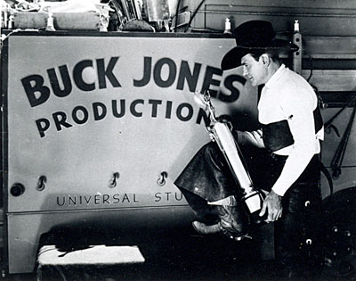 Buck Jones holds a trophy for ?? in front of a Universal Studios sign for his Buck Jones Productions '34-'37.
