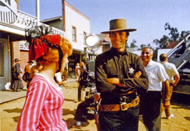 "On the Universal backlot, Clint Eastwood shares a joke with actress Arlene Golonka during the filming of ""Hang 'Em High"". That's director Ted Post approaching the couple."