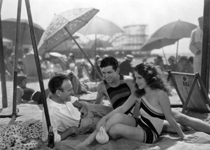 A day at the beach with director Sam Wood, Johnny Mack Brown and Norma Shearer.