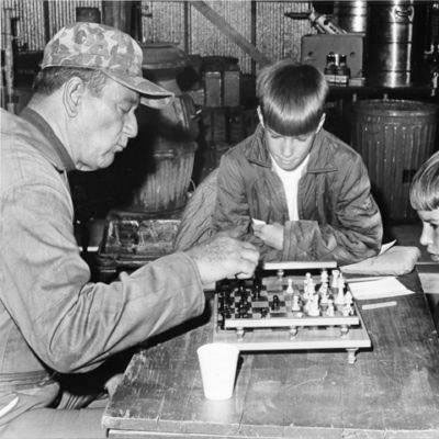 "John Wayne teaches some youngsters the art of playing Chess during a break from filming ""Hellfighters"". (Thanx to Bobby Copeland.)"