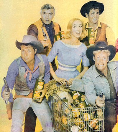 "Protecting Mrs. Smart Buyer and her cart full of Del Monte products are Lorne Greene and Michael Landon of ""Bonanza"", John Smith of ""Laramie"" and Doug McClure of ""Overland Trail""."