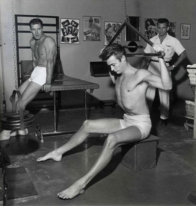 Meanwhile, in another gym, Jock Mahoney takes a break and watches Clint Eastwood work out.