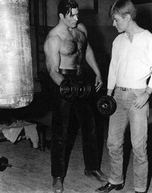 "In between working on their Warner Bros. shows, Clint ""Cheyenne"" Walker instructs Will ""Sugarfoot"" Hutchins on the proper use of gym weights."