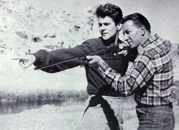 "Actor Don Murray and Hollywood's leading technical expert on weapons, Rodd Redwing, work on a scene for ""From Hell to Texas"" ('58). In the movie Rodd fired live ammo from a .30 caliber M1 into a watering trough behind which Murray was hiding. Midway through the trough Rodd had placed a steel plate to stop the bullets. The holes and spurs of water that resulted made the scene very realistic. Then as Murray ran from behind the trough Rodd expertly followed him with a barrage that kicked up dust just inches from Murray's heels."