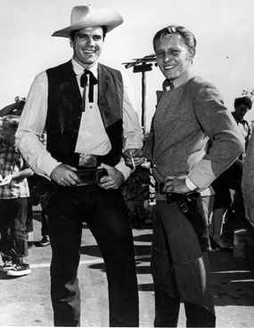 "Tom Tryon (""Texas John Slaughter"") and Jan Merlin (""Rough Riders"") pose together at a 1958 charity event. The pair had previously worked together on ""Screaming Eagles"" in 1956."