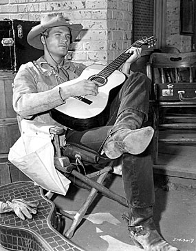 "Ty Hardin relaxes with his guitar on the set of Warner Bros.' ""Bronco"" in 1960."