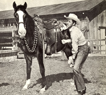 Audie Murphy attends to the hoof of one of his race horses.