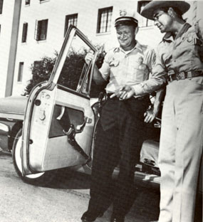 TV's U.S. Marshal, John Bromfield, admires Tucson policeman Jimmy Adcock's rifle outside the old Pima County Courthouse.