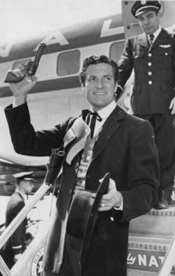 "Hugh ""Wyatt Earp"" O'Brian waves to the crowd as he departs an airplane in the '50s. Yep, he got away with guns on an airplane back then."