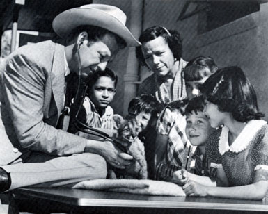 "While appearing at the Tucson, AZ, Rodeo in February, 1957, Rex Allen, then starring as TV's ""Frontier Doctor"", examines an eight week old cougar cub from the Arizona-Sonora Desert Museum. Dorothy Jones, Allen's teacher when he was a boy in Willcox, watches with some of her students from Davis School—Willie Canez, Joe Carmaliche, Sylvia Glass, Jimmy Wilkie and Mary Helen Young."