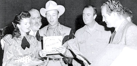 "Dale Evans, Gabby Hayes, Roy Rogers and three members of the Riders of the Purple Sage (Al Sloey, Scotty Harrell [face hidden] and Foy Willing) prepare to make a recording of ""Along the Navajo Trail"" for the weekly Roy Rogers radio program in the late '40s."
