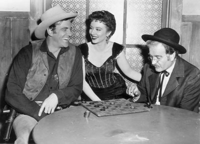 "Matt (James Arness) and Doc (Milburn Stone) engage in a friendly game of checkers between ""Gunsmoke"" scenes as Miss Kitty (Amanda Blake) looks on."