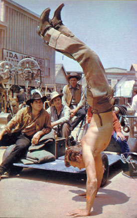 "Clint Eastwood limbers up between takes on the set of ""Rawhide""."