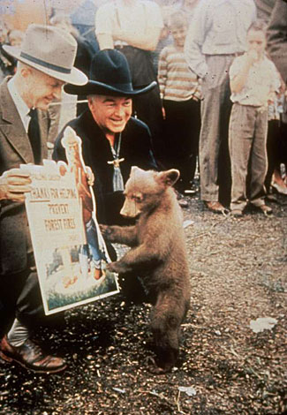 Hopalong Cassidy and Smokey the Bear thank the folks for helping to prevent forest fires.