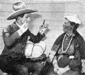 Tom Mix in 1923 explaining to an Indian lady what a razor and shaving is all about.