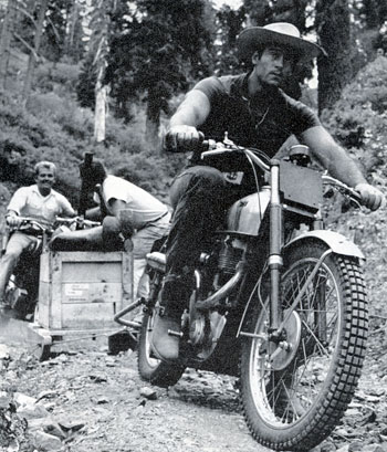 Cint Walker, while panning for gold in the south fork of California's Feather River, hops on his motorcycle to tow an equipment laden sled by rope. The several hundred pound load included gear, dynamite and aqua lungs.
