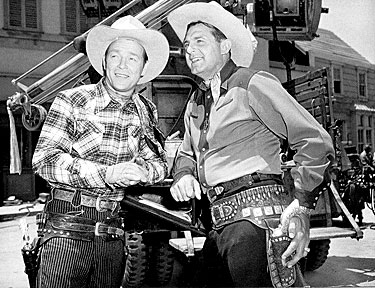 "Roy Rogers and Ray ""Crash"" Corrigan on the Republic backlot during the filming of ""Trail of Robin Hood"" ('50)."