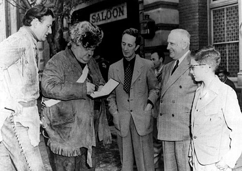 "Alongside John Wayne, while making ""The Fighting Kentuckian"" ('49), Oliver Hardy signs an autograph for noted artist Norman Rockwell (center)."