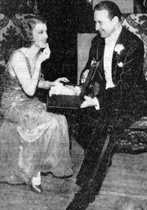 Monte Blue, featured in many Westerns from the silent era on through early television, assists Jeanette McDonald with her makeup before their act went on at the 1931 annual Christmas benefit show at the Shrine Civic Auditorium in L.A.