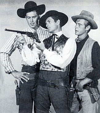 "Hugh ""Wyatt Earp"" O'Brian shows off his Buntline Special to Clint ""Cheyenne"" Walker and John Lupton of ""Broken Arrow""."