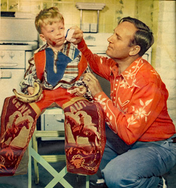 Gene Autry cleans up the face of little Jeffrey Burch after the youngster had a slight accident with his jelly sandwich. Gene and Ina were babysitting for Gene's radio  program producer Bill Burch and his wife in October 1950.